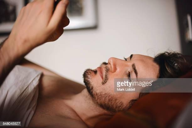 Handsome men in bed texting