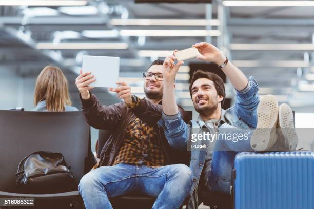 Handsome men taking selfie with smart phone and digital pc