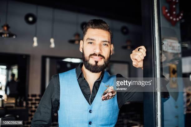 handsome mitte adult barbier am eingang des stores - westen stock-fotos und bilder
