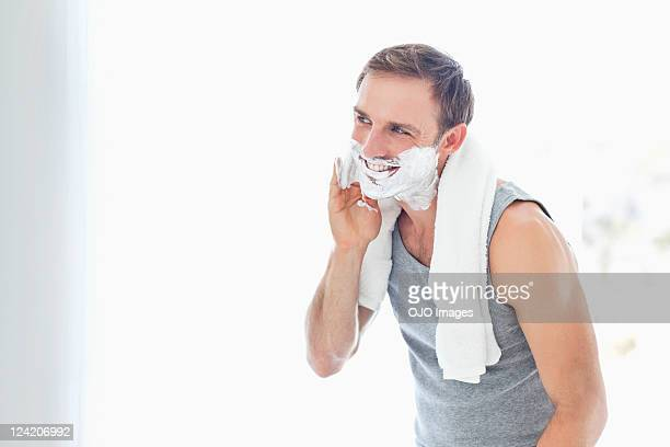 handsome mid adult man applying shaving cream - shaving cream stock photos and pictures