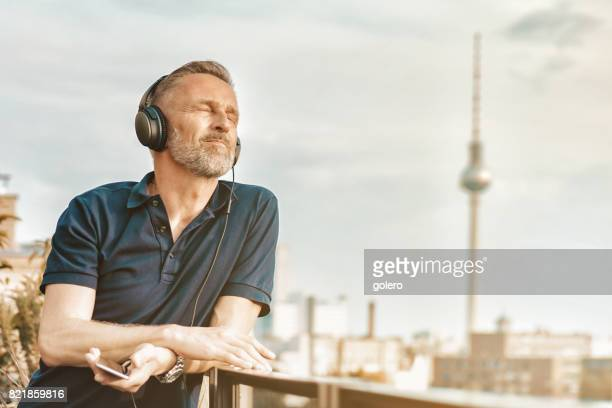 handsome midaged man with headphones and mobile at balcony - central berlin stock photos and pictures