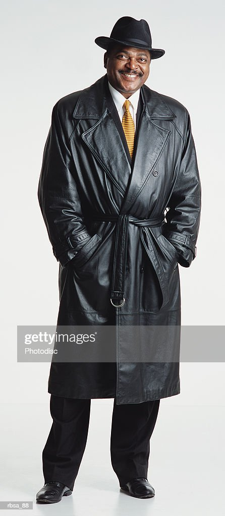 handsome middle aged adult african american male with a moustache and hat wears a dark leather trench coat and white shirt and tie while standing and looking at the camera smiling approvingly : Foto de stock