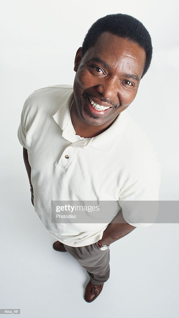 handsome middle aged african american adult male with a moustache wearing a white polo shirt and gray slacks stands looking up at the camera smiling confidently : Foto de stock