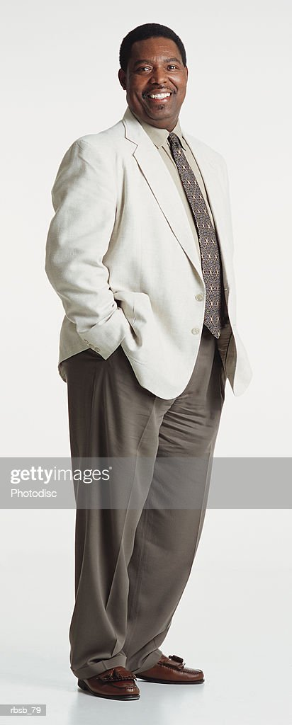 handsome middle aged african american man dressed in a light blazer and brown pants looking into the camera with his hands in his pockets : Foto de stock