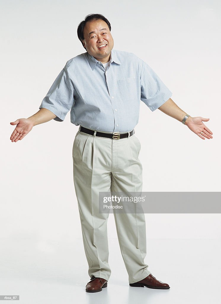 handsome middle aged asian adult male wearing a light blue short sleeved shirt and cream colored slacks stands with shrugged shoulders and hands in the air as he looks at the camera with a anxious smile : Stock Photo