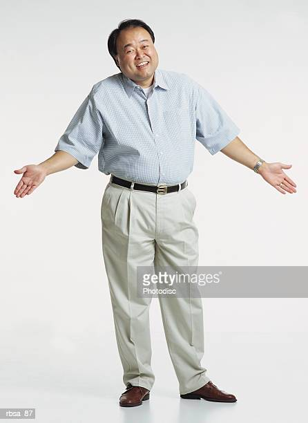 handsome middle aged asian adult male wearing a light blue short sleeved shirt and cream colored slacks stands with shrugged shoulders and hands in the air as he looks at the camera with a anxious smile