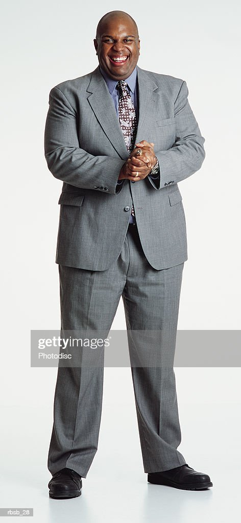 handsome middle aged bald african american man in light grey suit stands laughing looking to camera : Foto de stock