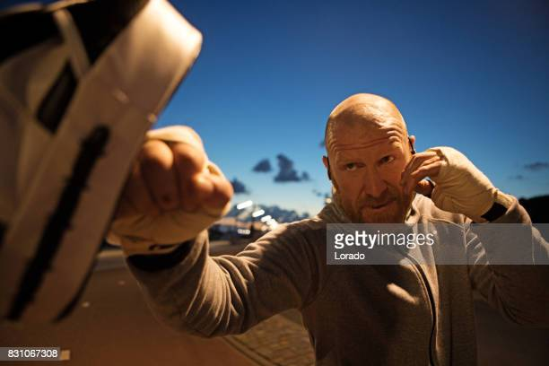 handsome middle aged bearded man boxing outdoors in northern europe - mixed martial arts stock pictures, royalty-free photos & images