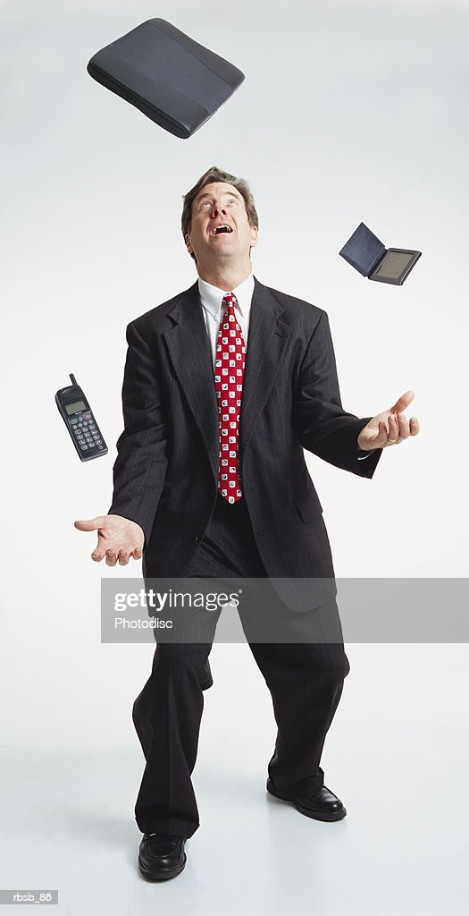 handsome middle aged caucasian businessman dark suit juggles laptop computer palm pilot cell phone : Stockfoto
