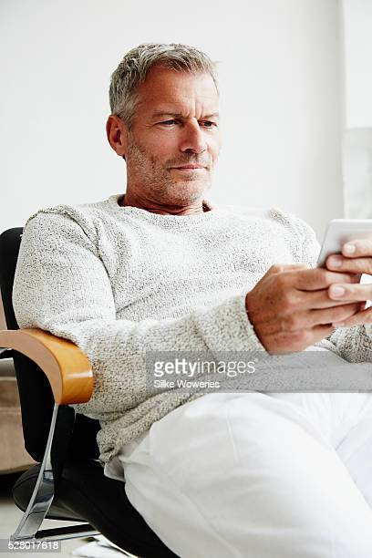handsome middle-aged man sitting in his office - handsome 50 year old men stock photos and pictures