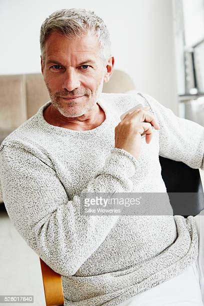 handsome middle-aged man sitting in his office - handsome 50 year old men stock pictures, royalty-free photos & images