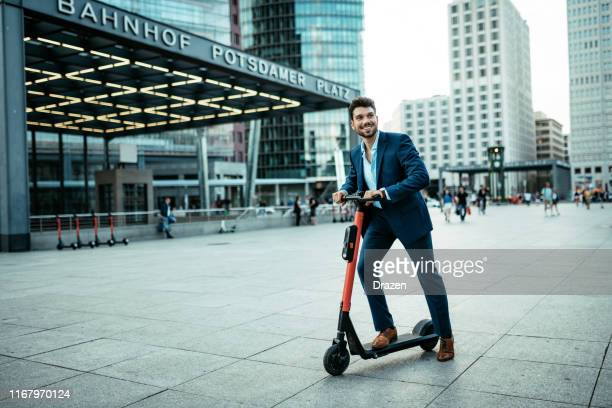 handsome millennial businessman on electric scooter going to work - electric scooter stock pictures, royalty-free photos & images