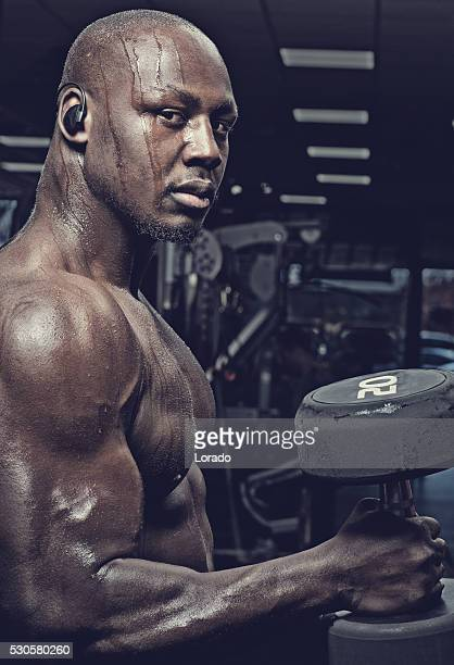 Handsome muscled black male exercising with weights in a gym