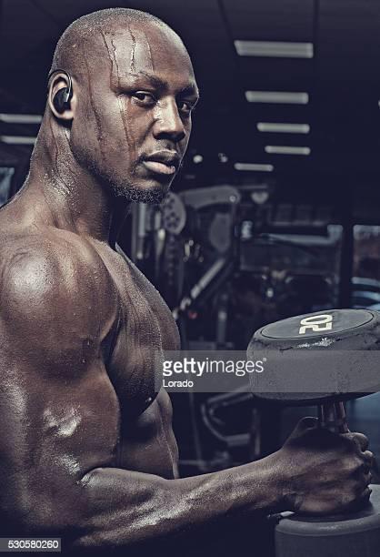 Atractivo musculosa negro macho hacer ejercicios con pesas en el gimnasio