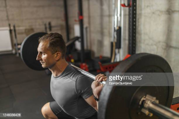 handsome muscular man doing squat exercise with barbell at the gym - mid adult stock pictures, royalty-free photos & images