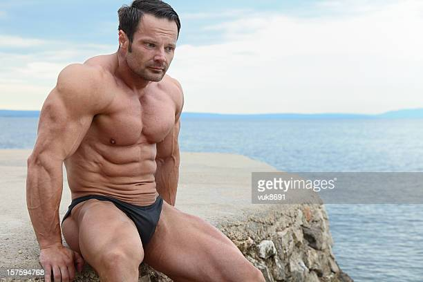 Handsome muscular man sitting on the beach