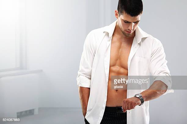 handsome muscular man with a wristwatch. - shirt stock pictures, royalty-free photos & images