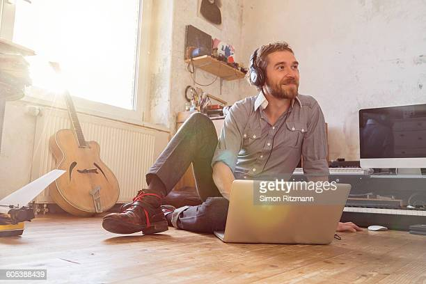 Handsome musician with headphones using laptop