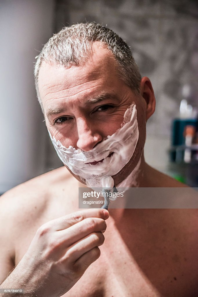Handsome Naked Man Shaving Using A Razor And Looking Away Stock Photo