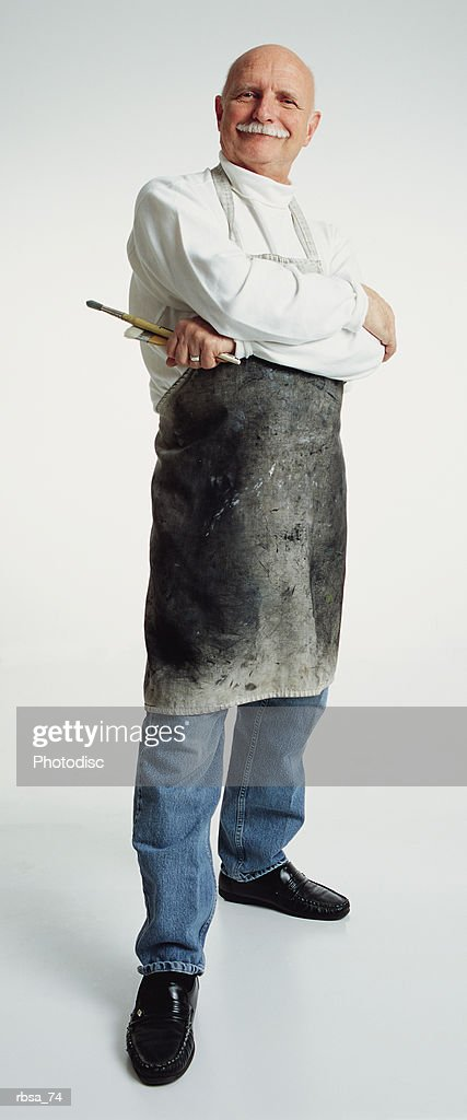 handsome old bald adult caucasian male with moustache wearing white turtleneck and painters apron stands holding paintbrushes while looking at camera with satisfied smile : Foto de stock