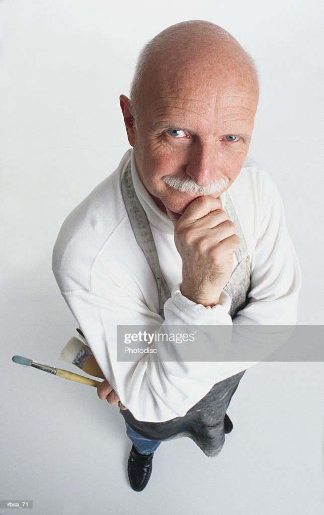 handsome old blue eyed adult caucasian balding male with a moustache wearing a white turtleneck and a painters apron while holding paint brushes with has his hand on his chin as he looks thoughtfully up at the camera : Foto de stock