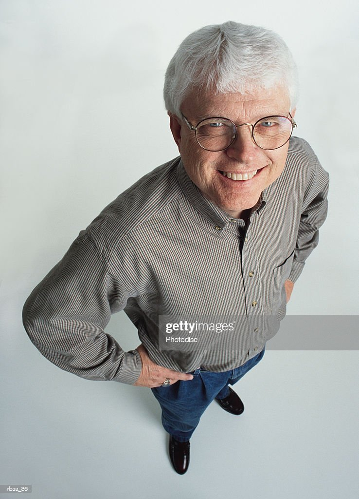 handsome old caucasian adult male white hair glasses wears gray shirt jeans stands smiles to camera : Foto de stock