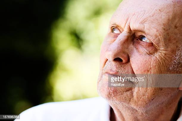 Handsome old man looks to side, frowning