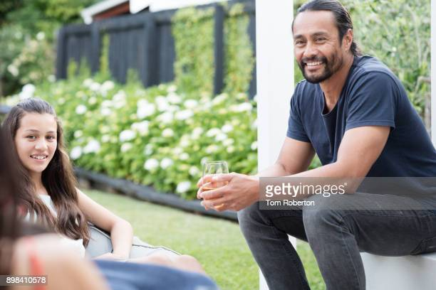 Handsome pacific island man and daughter relaxing in back yard