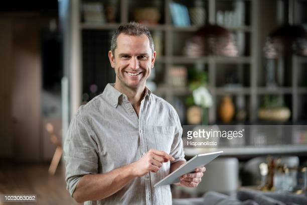 handsome real estate agent at an apartment holding a tablet while looking at camera smiling - salesman stock pictures, royalty-free photos & images