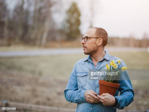 Handsome real man outdoors in nature in spring with daffodils