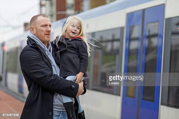Knappe roodharige middelbare leeftijd vader en schattige blonde dochter reizen op openbaar vervoer