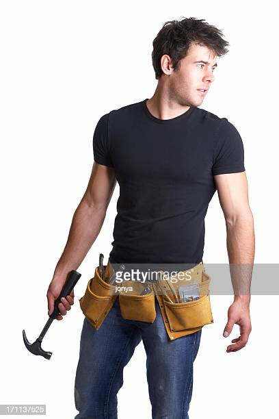 Handsome repairman wearing tool belt with hammer in hand
