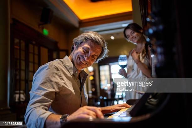 レストランで彼の妻のためにピアノを弾くハンサムなロマンチックな夫 - キーボード奏者 ストックフォトと画像