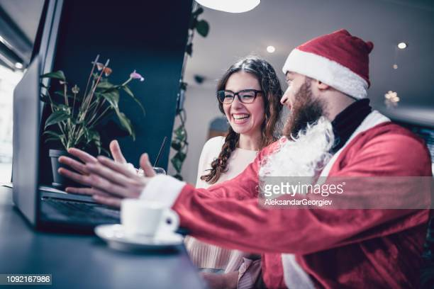 Handsome Santa And His Cute Assistant Watchin Funny Videos On Laptop