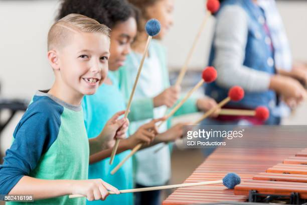 Handsome schoolboy plays marimba during percussion class