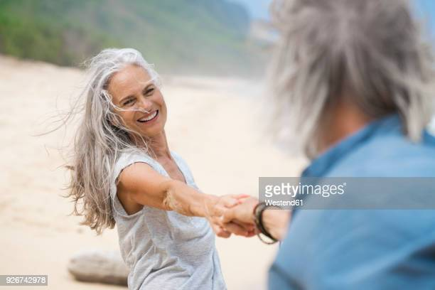 handsome senior couple dancing on the beach - 60 64 years stock pictures, royalty-free photos & images