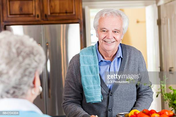 Handsome senior man cooking in a kitchen for her wife
