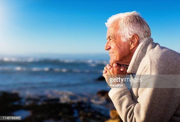 homme aîné beau regards dehors à la mer - un seul homme photos et images de collection