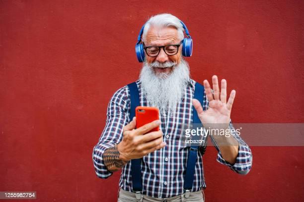 knappe hogere mens die videovraag maakt - alleen seniore mannen stockfoto's en -beelden