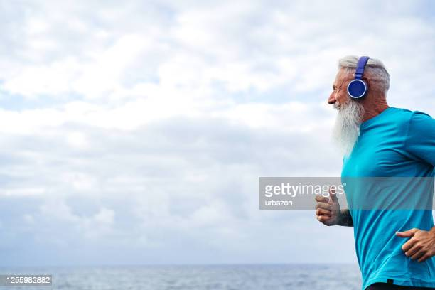 handsome senior man running - active lifestyle stock pictures, royalty-free photos & images