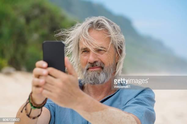Handsome senior man taking a picture with smartphone on the beach