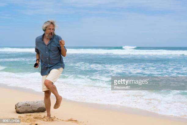 handsome senior man with headphones dancing on the beach - man dancing stock pictures, royalty-free photos & images