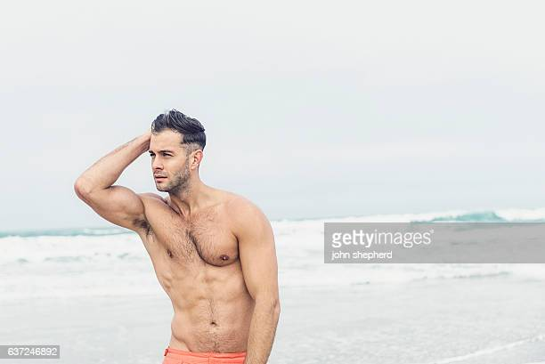 handsome shirtless man at the beach. - hairy chest stockfoto's en -beelden