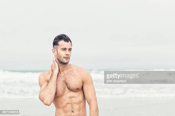 handsome shirtless man at the beach.