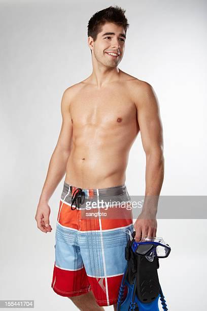 Handsome shirtless man in swim trunks holding snorkel gear smiling