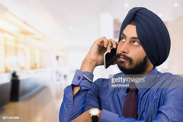 Handsome sikh businessman talking on phone