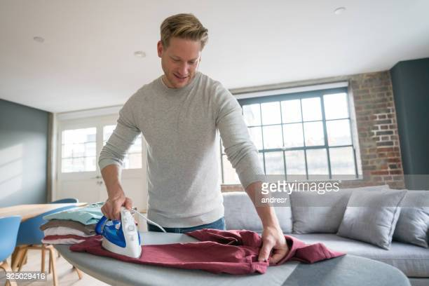 Handsome single guy at home ironing his clothes looking happy