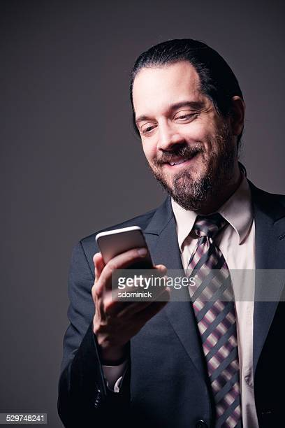 handsome smiling bearded man reading text - hairy man stock pictures, royalty-free photos & images