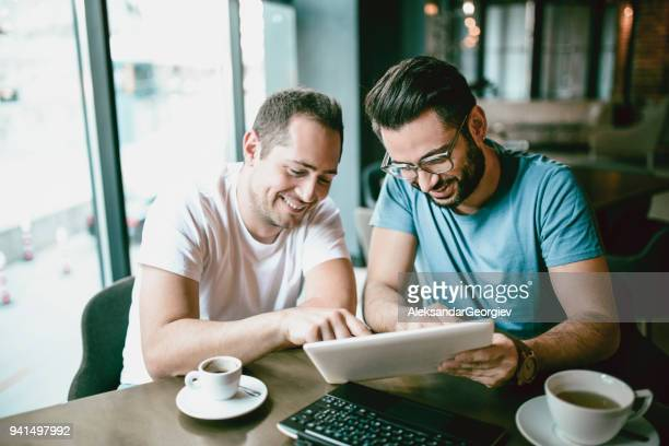 handsome smiling freelancer showing finished project on digital tablet to a colleague in coffee restaurant - casal homossexual imagens e fotografias de stock
