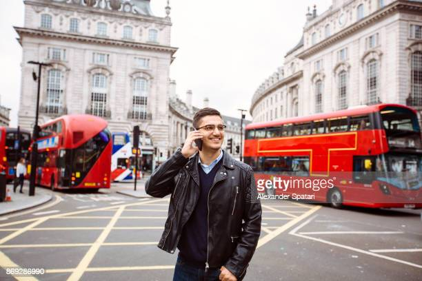 Handsome smiling guy talking on the phone on Piccadilly Circus, London, UK